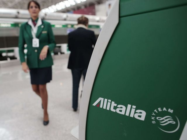 An Alitalia worker walks near an Alitalia auto check-in machine at Fiumicino airport in Rome October 11, 2013. Alitalia, the Italian national airline that has made a profit only a few times in its 67-year history, once again risks collapsing as the government scrambles to find investors willing to rescue its problem child. Rome offered a financial lifeline to Alitalia through the state-owned post office, but the plan depends on private shareholders ploughing more money into what many investors regard as a corporate lost cause. REUTERS/Tony Gentile (ITALY - Tags: POLITICS TRANSPORT BUSINESS EMPLOYMENT)